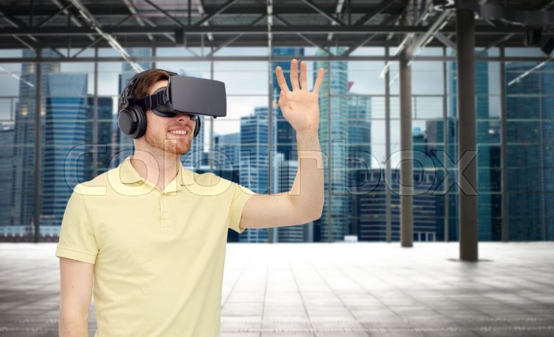 Stock image of '3d technology, virtual reality, entertainment and people concept - happy young man with virtual reality headset or 3d glasses playing game over industrial empty room and city panorama background'