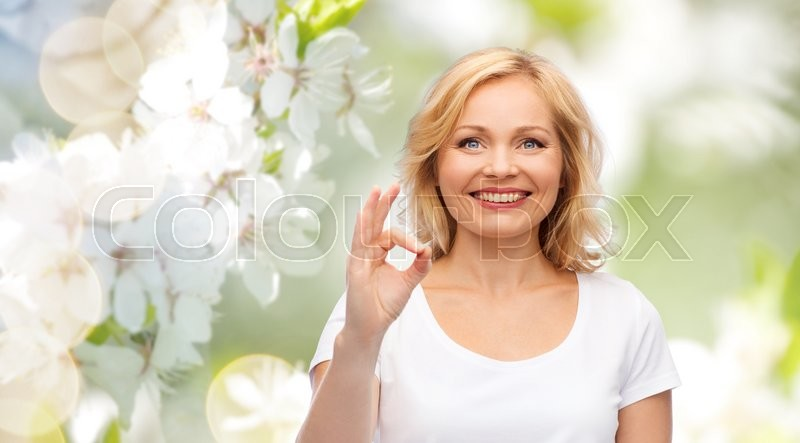 Stock image of 'gesture, advertisement and people concept - smiling woman in blank white t-shirt showing ok hand sign over natural spring cherry blossom background'