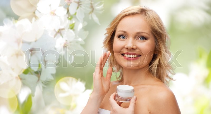 Stock image of 'beauty, people, skincare and cosmetics concept - happy woman applying cream to her face over natural spring cherry blossom background'