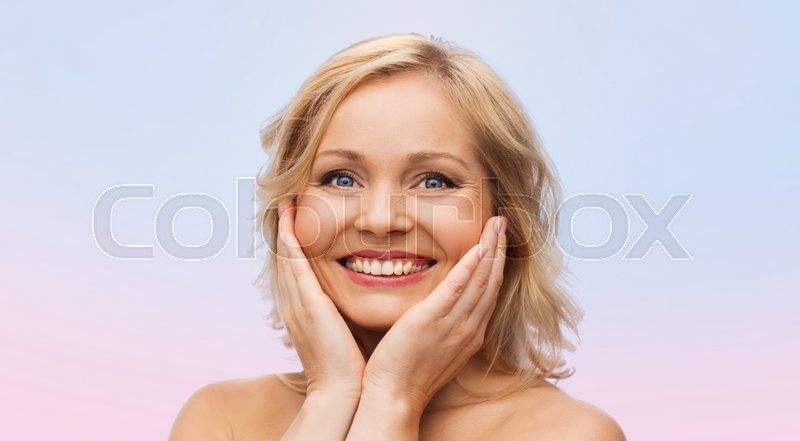 Stock image of 'beauty, people and skincare concept - smiling woman with bare shoulders touching face over rose quartz and serenity gradient background'
