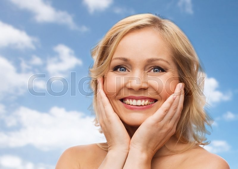 Stock image of 'beauty, people and skincare concept - smiling woman with bare shoulders touching face over blue sky and clouds background'