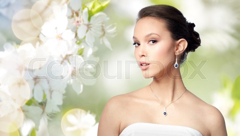 Stock image of 'beauty, jewelry, wedding accessories, people and luxury concept - beautiful asian woman or bride with earring and pendant over natural spring cherry blossom background'