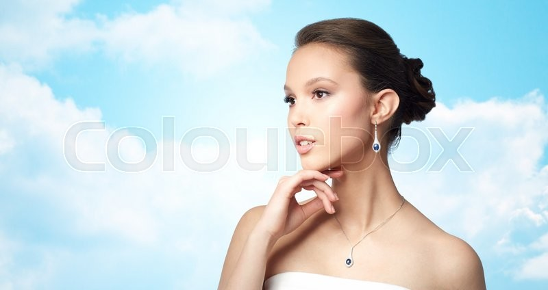 Stock image of 'beauty, jewelry, wedding accessories, people and luxury concept - beautiful asian woman or bride with earring and pendant over blue sky and clouds background'