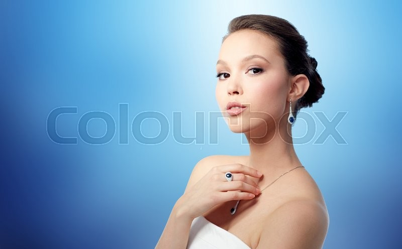 Stock image of 'beauty, jewelry, people and luxury concept - beautiful asian woman or bride with earring, finger ring and pendant over blue background'