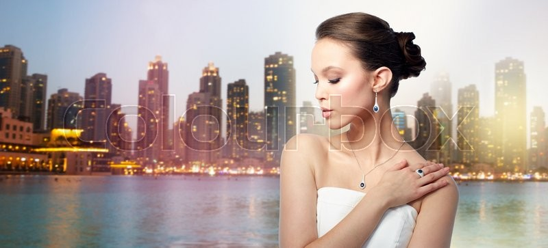 Stock image of 'beauty, jewelry, people and luxury concept - beautiful asian woman or bride with earring, finger ring and pendant over evening dubai city lights and skyscrapers background'