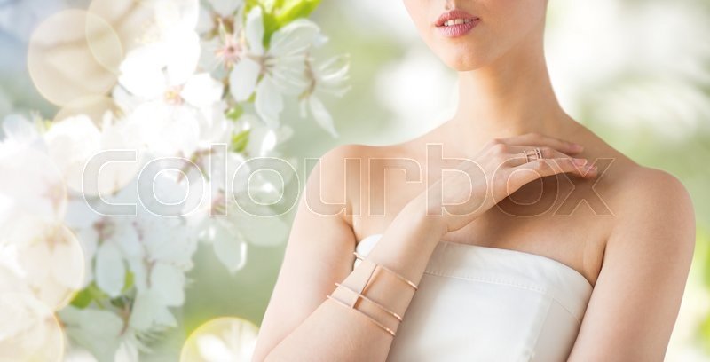 Stock image of 'glamour, beauty, jewelry and luxury concept - close up of beautiful woman with golden ring and bracelet over natural spring cherry blossom'