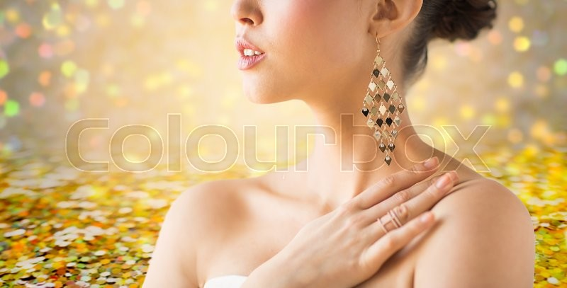Stock image of 'glamour, beauty, jewelry and luxury concept - close up of beautiful woman with earrings over golden holidays lights background'