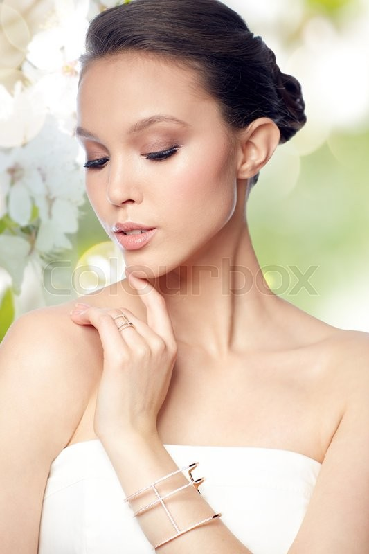 Stock image of 'beauty, jewelry, wedding accessories, people and luxury concept - beautiful asian woman or bride with golden ring and bracelet over natural spring cherry blossom background'