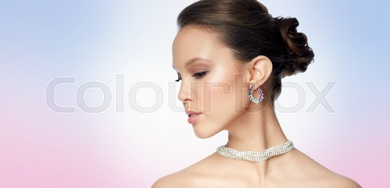 Stock image of 'beauty, jewelry, accessories, people and luxury concept - close up of beautiful asian woman face with earring over rose quartz and serenity gradient background'