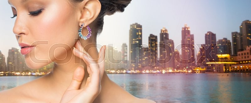 Stock image of 'glamour, beauty, jewelry and luxury concept - close up of beautiful woman face with earring over singapore city skyscrapers background'
