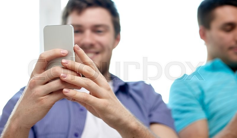 Stock image of 'friendship, technology and people concept - close up of happy smiling male friends with smartphones texting at home'