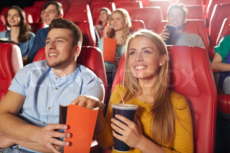 Stock image of 'cinema, entertainment and people concept - happy friends watching movie in theater'