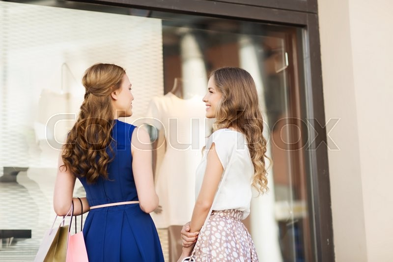 Stock image of 'sale, consumerism and people concept - happy young women with shopping bags talking at to shop window in city from back'