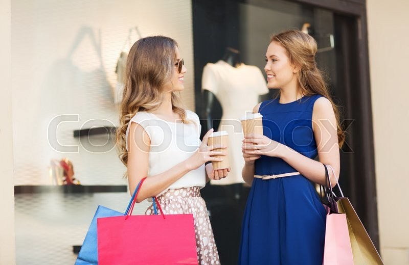 Stock image of 'sale, consumerism and people concept - happy young women with shopping bags and coffee paper cups talking at shop window in city'
