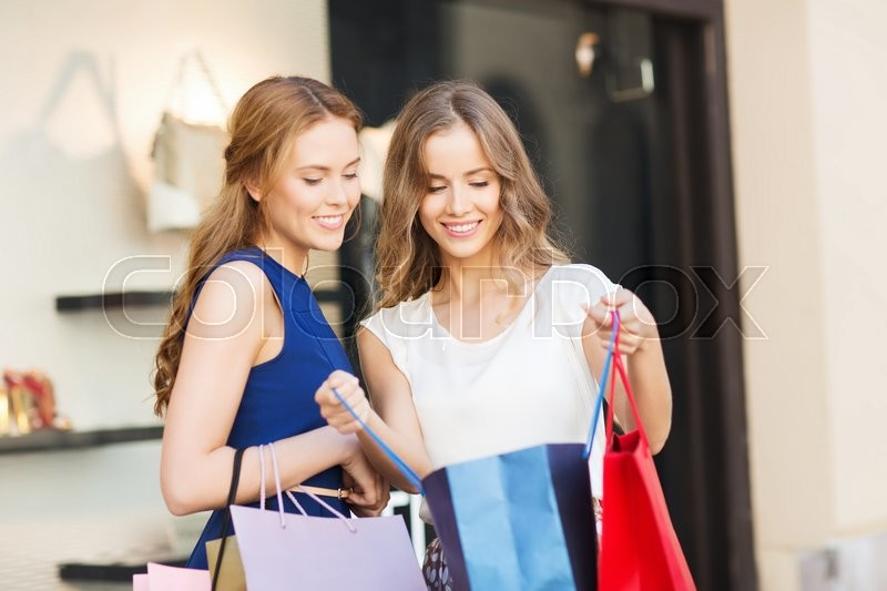Stock image of 'sale, consumerism and people concept - happy young women looking into shopping bags at shop window in city'