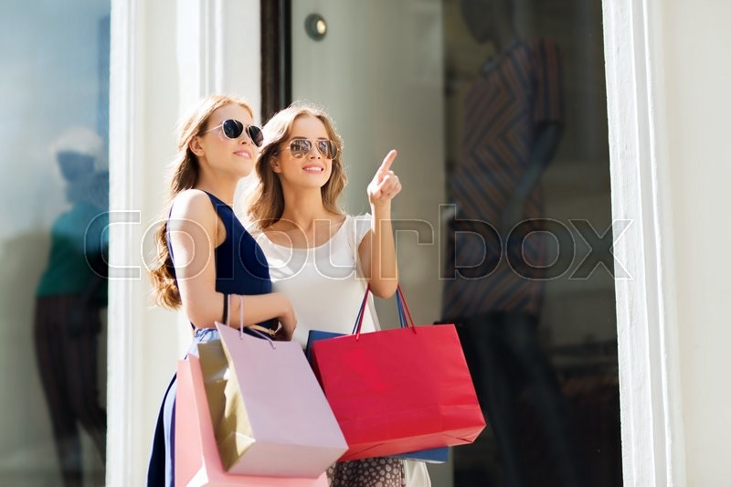 Stock image of 'sale, consumerism and people concept - happy young women with shopping bags pointing finger outdoors'