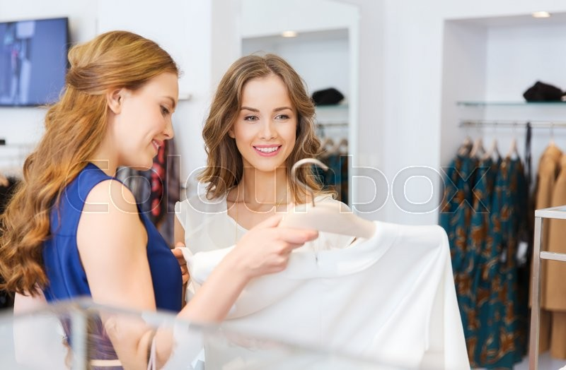 Stock image of 'sale, consumerism and people concept - happy young women with shopping bags choosing clothes at clothing shop'