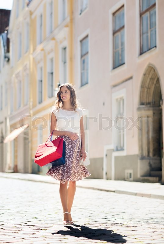 Stock image of 'sale, consumerism and people concept - happy young woman with shopping bags walking along city street'