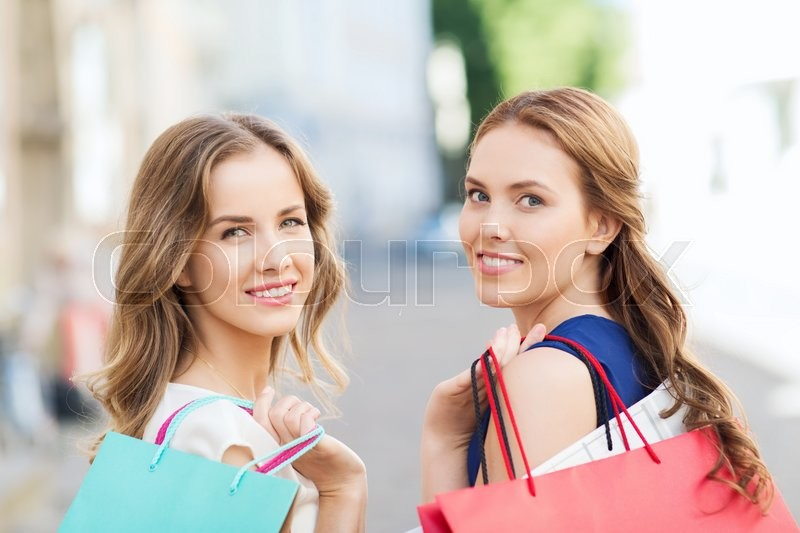 Stock image of 'sale, consumerism and people concept - happy young women with shopping bags walking along city street'