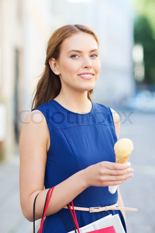 Stock image of 'sale, consumerism, summer and people concept - happy young woman with shopping bags and ice cream on city street'