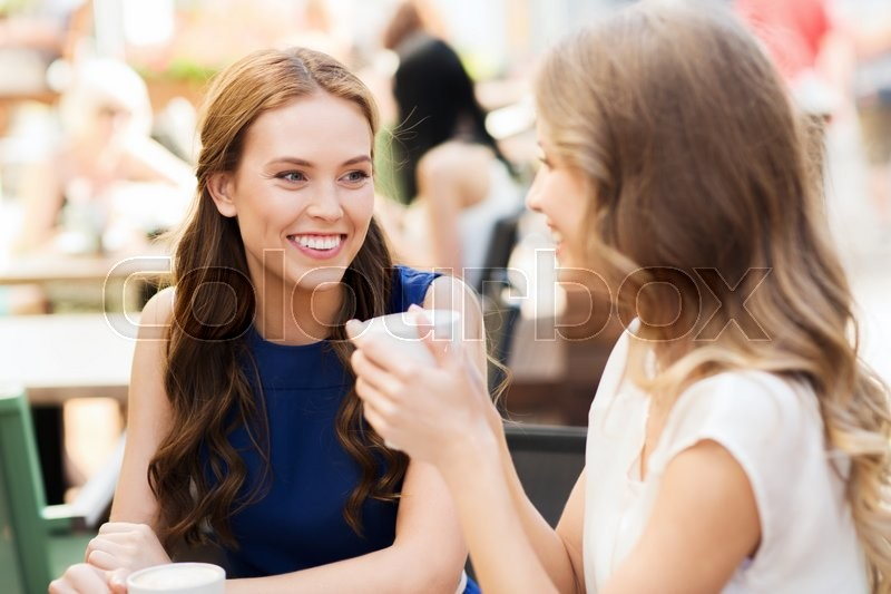 Stock image of 'communication and friendship concept - smiling young women with coffee cups at cafe'