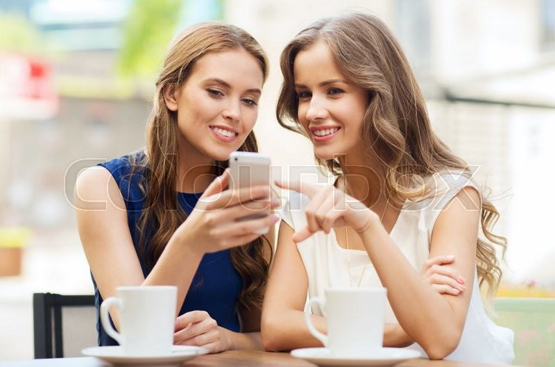 Stock image of 'technology, lifestyle, friendship and people concept - happy young women or teenage girls with smartphone and coffee cups at outdoor cafe'