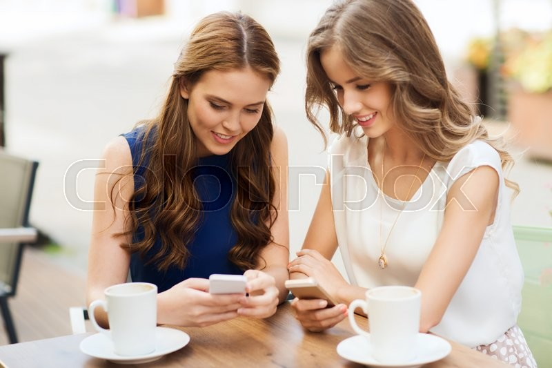 Stock image of 'technology, lifestyle, friendship and people concept - happy young women or teenage girls with smartphones and coffee cups at cafe outdoors'