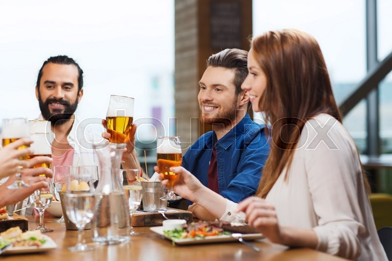 Stock image of 'leisure, eating, food and drinks, people and holidays concept - smiling friends having dinner and drinking beer at restaurant or pub'