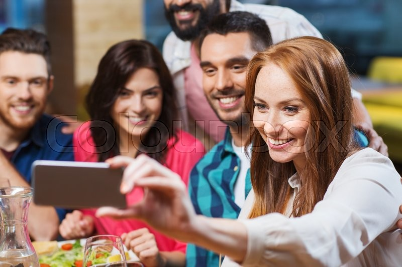 Stock image of 'leisure, technology, friendship, people and holidays concept - happy friends having dinner and taking selfie by smartphone at restaurant'