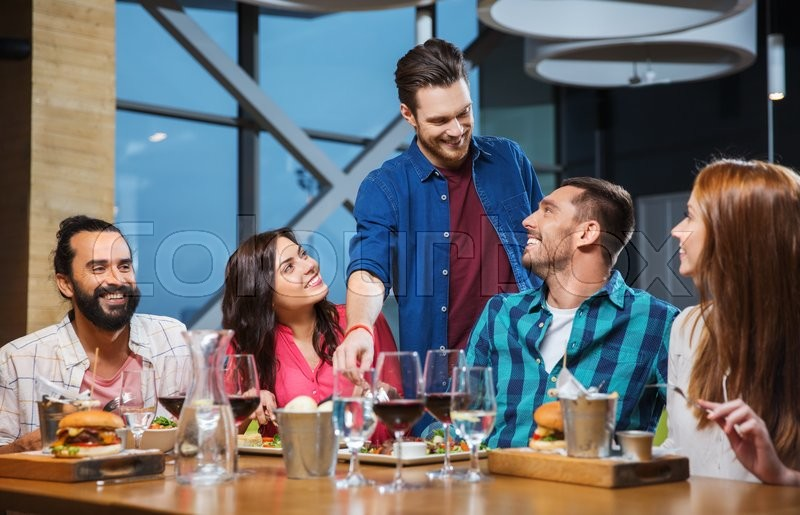 Stock image of 'leisure, eating, food and drinks, people and holidays concept - smiling friends having dinner and drinking red wine at restaurant'
