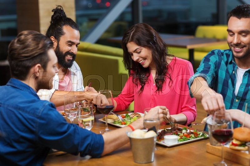 Stock image of 'leisure, eating, food, people and holidays concept - smiling friends having dinner and tasting each other dish at restaurant'