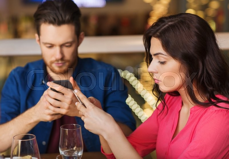 Stock image of 'leisure, technology, lifestyle and people concept - couple with smartphones dining at restaurant'