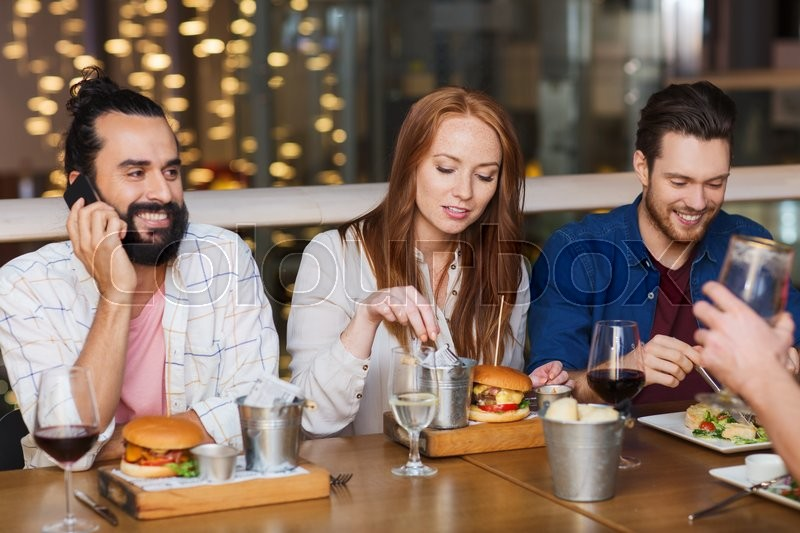 Stock image of 'leisure, technology, lifestyle and people concept - happy man with smartphone and friends dining at restaurant'