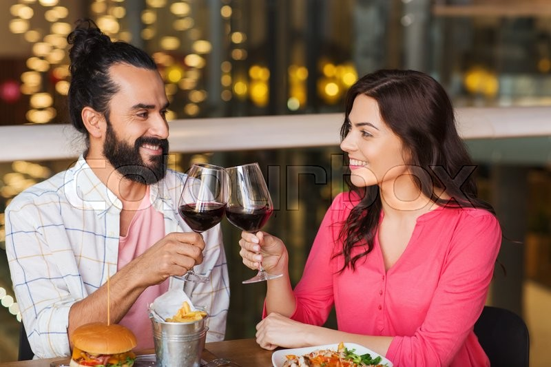 Stock image of 'leisure, celebration, food and drinks, people and holidays concept - smiling couple having dinner and drinking red wine at date in restaurant'