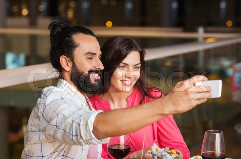 Stock image of 'leisure, technology, date, people and holidays concept - happy couple having dinner and taking selfie by smartphone at restaurant'