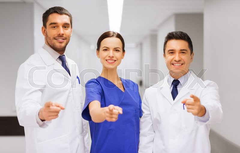 Stock image of 'clinic, profession, people, health care and medicine concept - group of happy medics or doctors pointing finger on you at hospital corridor'