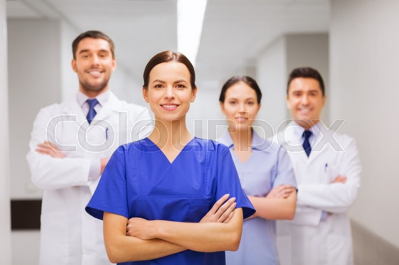 Stock image of 'clinic, profession, people, health care and medicine concept - happy group of medics or doctors at hospital corridor'