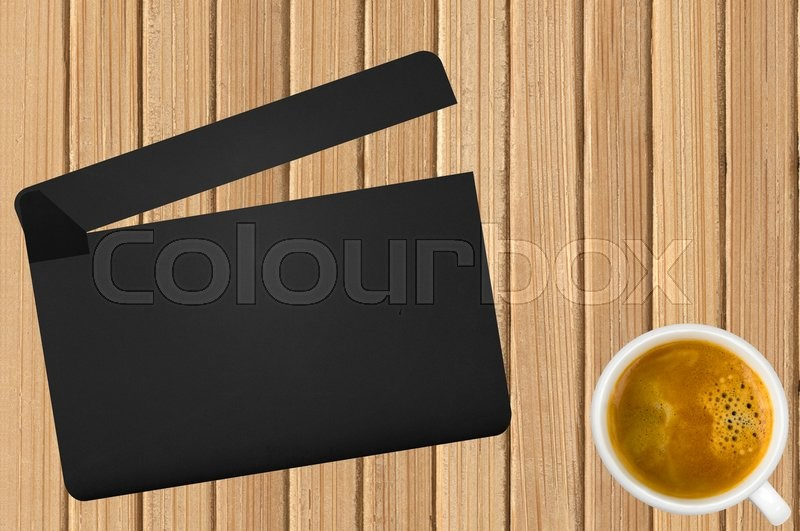 Stock image of 'Movie clapper and coffee cup on wooden background'