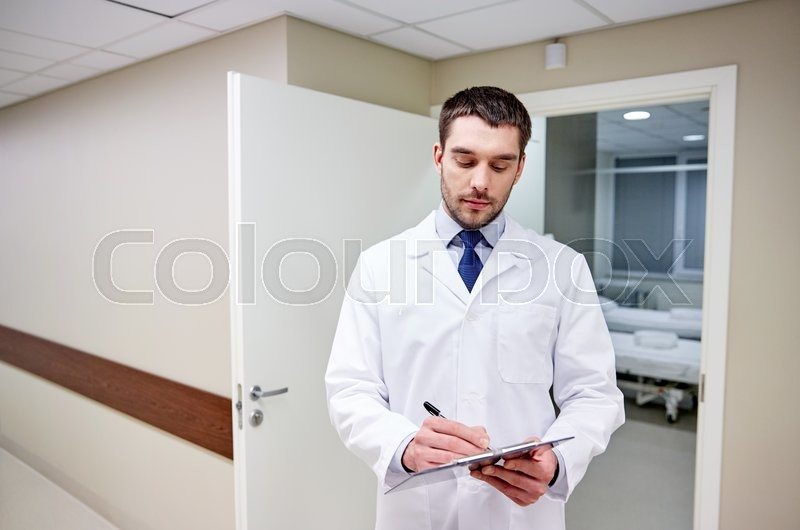 Stock image of 'clinic, profession, people, health care and medicine concept - doctor with clipboard at hospital corridor'