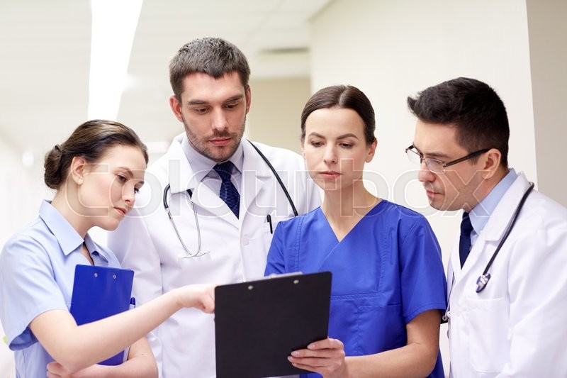Stock image of 'clinic, profession, people, health care and medicine concept - group of medics or doctors with clipboard at hospital corridor'
