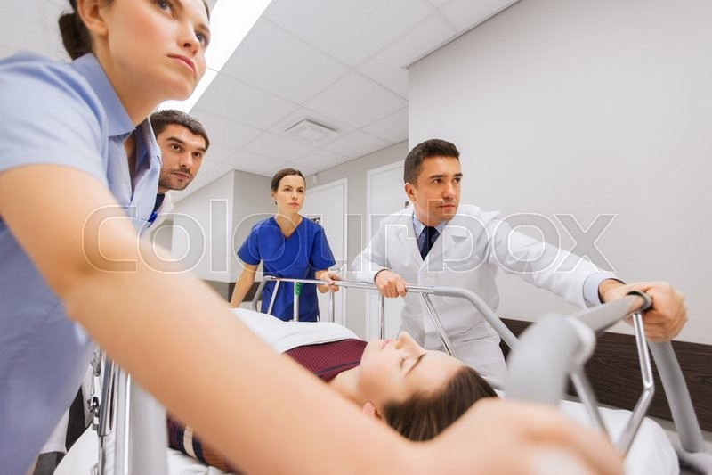 Stock image of 'profession, people, health care, reanimation and medicine concept - group of medics or doctors carrying unconscious woman patient on hospital gurney to emergency'