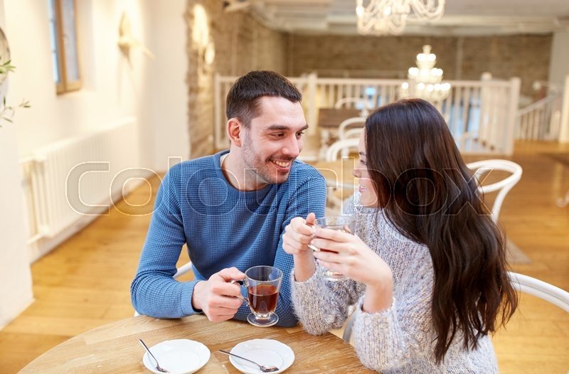Stock image of 'people, communication and dating concept - happy couple drinking tea at cafe or restaurant'