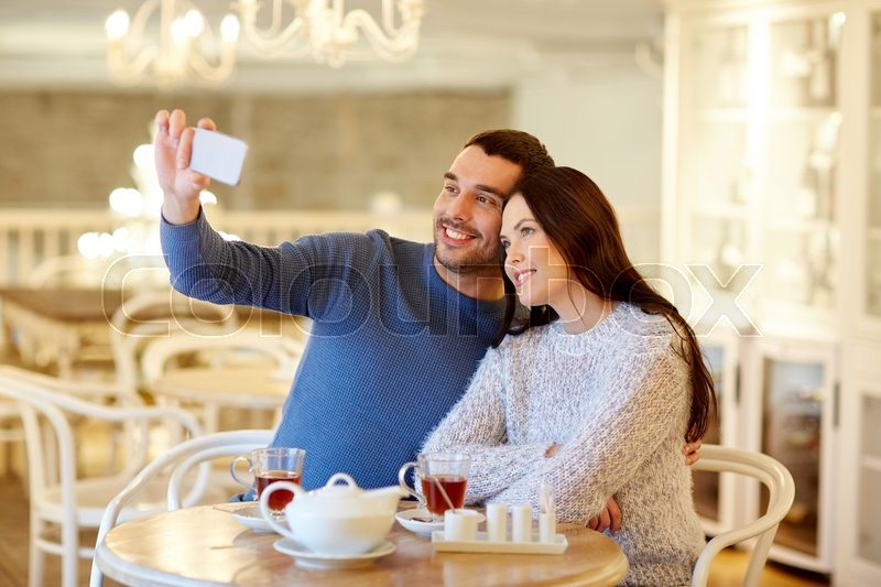 Stock image of 'people, technology and dating concept - happy couple taking smartphone selfie and drinking tea at cafe or restaurant'