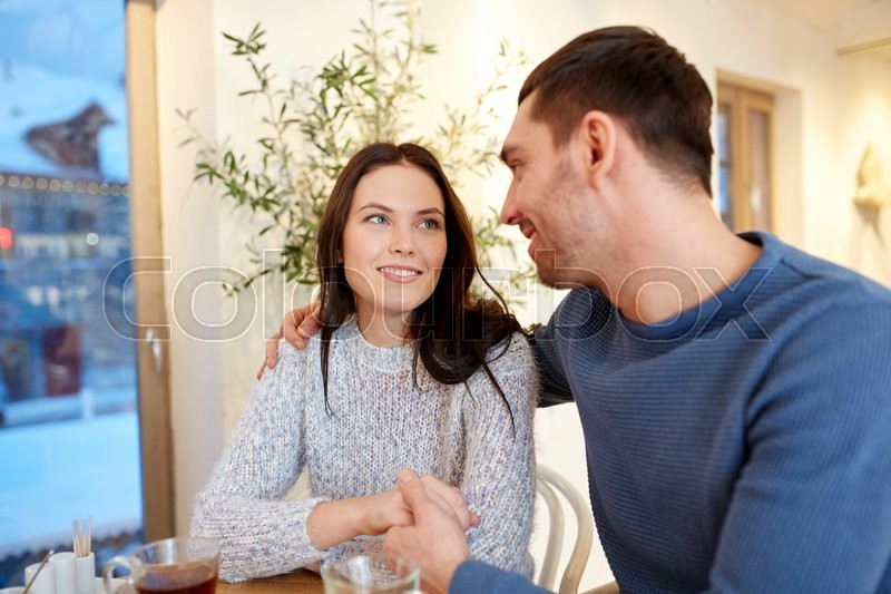 Stock image of 'people, communication and dating concept - happy couple drinking tea and hugging at cafe or restaurant'