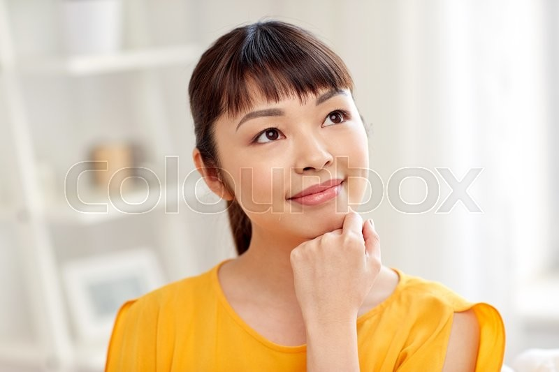 Stock image of 'people, race, ethnicity and portrait concept - happy asian young dreaming woman or teenage girl face at home'