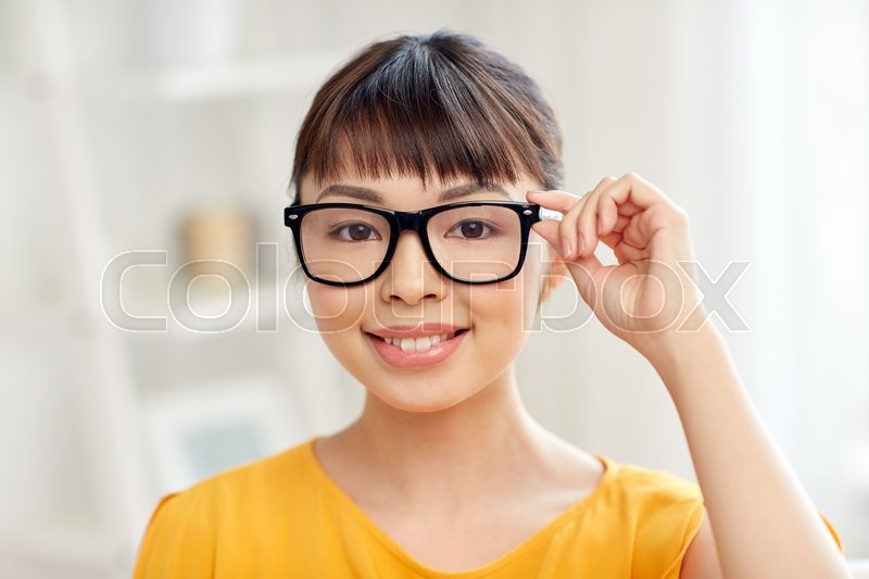 Stock image of 'people, education, vision and portrait concept - happy asian young woman or teenage student girl in glasses at home'