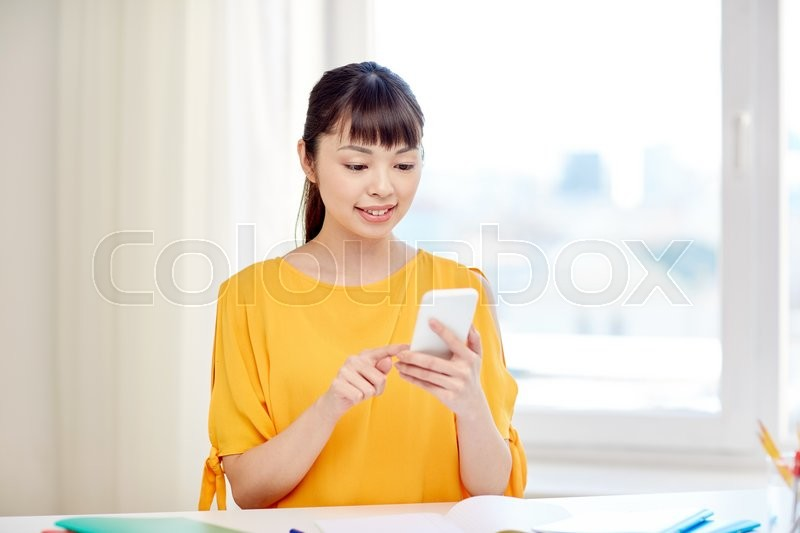 Stock image of 'people, education, high school, technology and learning concept - happy asian young woman student with smartphone texting message at home'