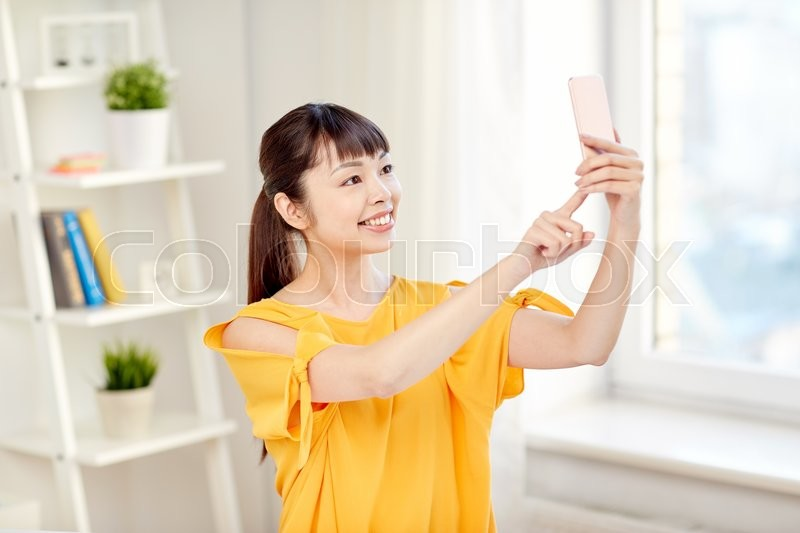 Stock image of 'people, technology and leisure concept - happy young asian woman taking selfie on smartphone at home'