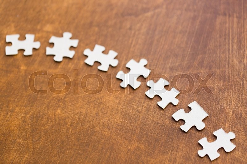 Stock image of 'business and connection concept - close up of puzzle pieces on wooden surface'