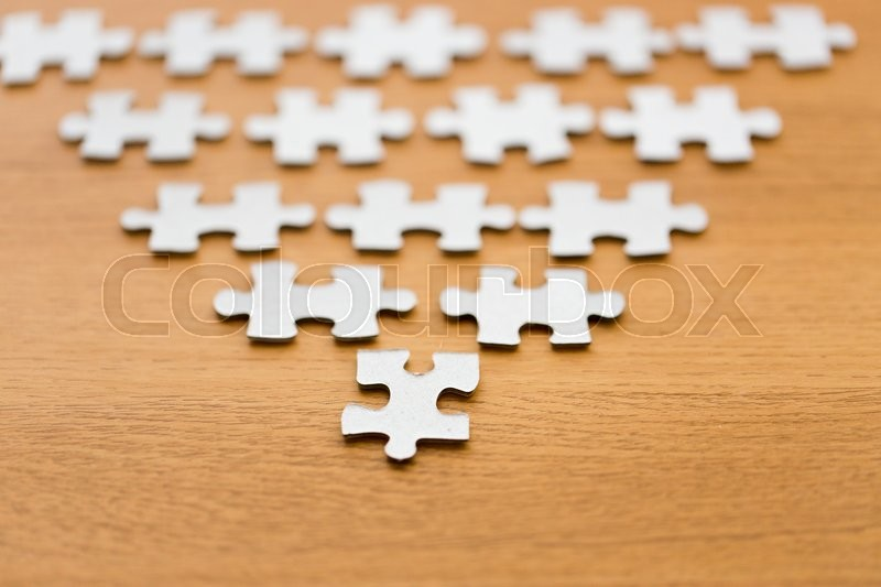 Stock image of 'business and connection concept - close up of puzzle pieces in pyramid shape on wooden surface'